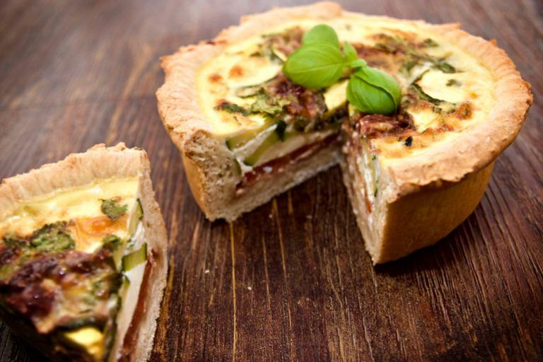 A delicious deep layered Mediterranean quiche with basil garnish.